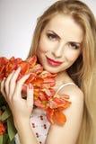 Schönes blondes Mädchen mit dem Blumenstrauß von den Tulpen lokalisiert auf einem w Stockfotografie