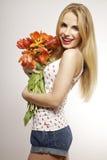 Schönes blondes Mädchen mit dem Blumenstrauß von den Tulpen lokalisiert auf einem w Lizenzfreies Stockfoto