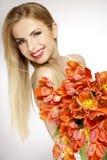 Schönes blondes Mädchen mit dem Blumenstrauß von den Tulpen lokalisiert auf einem w Lizenzfreie Stockfotografie