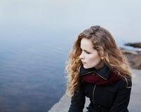 Schönes blondes Mädchen mit dem gelockten Haar, das auf den Banken des Flusses sitzt Stockbilder