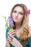 Schönes blondes Mädchen mit dem hellen Make-up, dem langen Kraushaar und enormen dem Schmuck, die eine blühende Niederlassung lok Lizenzfreies Stockfoto