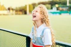 Schönes blondes Mädchen mit dem Lachen der blauen Augen lizenzfreie stockfotografie