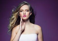 Schönes blondes Mädchen mit dem langen gelockten Haar über purpurrotem backgroun stockfotos