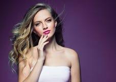 Schönes blondes Mädchen mit dem langen gelockten Haar über purpurrotem backgroun stockbilder