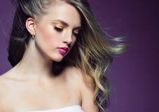 Schönes blondes Mädchen mit dem langen gelockten Haar über purpurrotem backgroun stockfoto