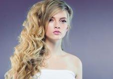Schönes blondes Mädchen mit dem langen gelockten Haar über purpurrotem backgroun stockfotografie