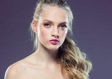 Schönes blondes Mädchen mit dem langen gelockten Haar über purpurrotem backgroun stockbild