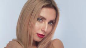 Schönes blondes Mädchen mit dem langen Haar, klassischem Make-up und roten den Lippen, die im Studio aufwerfen Schönes lächelndes stock footage