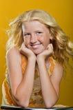 Schönes blondes Mädchen mit den Sommersprossen, die auf einem Stuhl und einem smilin sitzen Stockbild