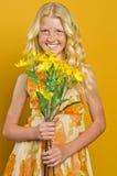 Schönes blondes Mädchen mit den Sommersprossen, die einen Blumenstrauß von Blumen halten Stockfotografie