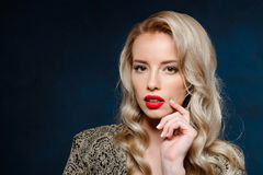 Schönes blondes Mädchen mit der Glättung des hellen Makes-up, das Kamera betrachtet Stockfotografie