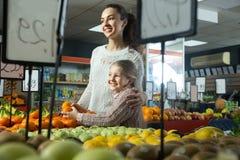 Schönes blondes Mädchen mit der Mutter, die Mandarinen am Speicher wählt Lizenzfreies Stockbild