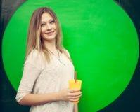 Schönes blondes Mädchen mit einem gelben Glas in der Hand, das nahe der grünen Wand aufwirft outdoor Stockbild