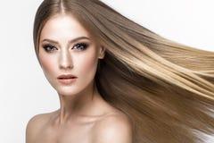 Schönes blondes Mädchen mit einem tadellos glatten Haar und klassisches Make-up Schönes lächelndes Mädchen Stockfoto