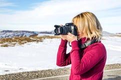 Schönes blondes Mädchen mit einer Kamera, zum von Fotos von kaukasischen Bergen zu machen Stockbilder