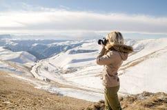 Schönes blondes Mädchen mit einer Kamera, zum von Fotos von kaukasischen Bergen zu machen Lizenzfreie Stockfotos