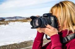 Schönes blondes Mädchen mit einer Kamera, zum von Fotos von kaukasischen Bergen zu machen Stockfotos