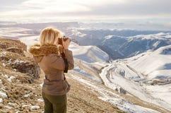 Schönes blondes Mädchen mit einer Kamera, zum von Fotos von kaukasischen Bergen zu machen Stockfotografie