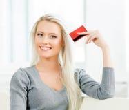 Schönes blondes Mädchen mit einer Kreditkarte Stockfotografie
