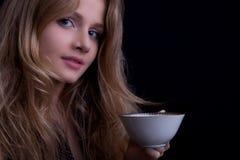 Schönes blondes Mädchen mit einer Tasse Tee schauend zur Kamera Lizenzfreies Stockbild