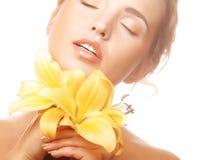Schönes blondes Mädchen mit gelber Lilie Lizenzfreie Stockfotografie