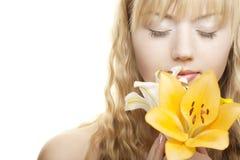 Schönes blondes Mädchen mit gelber Lilie Stockfotografie