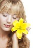 Schönes blondes Mädchen mit gelber Lilie Lizenzfreie Stockbilder