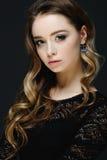 Schönes blondes Mädchen mit großen blauen Augen auf schwarzem Hintergrund Lizenzfreies Stockfoto