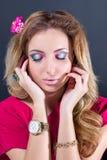Schönes blondes Mädchen mit hellem Make-up, dem langen Kraushaar und enormem Schmuck auf grauem Hintergrund Art und Weiseschuß Stockfotografie