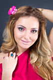 Schönes blondes Mädchen mit hellem Make-up, dem langen Kraushaar und enormem Schmuck auf grauem Hintergrund Art und Weiseschuß Stockbilder