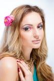 Schönes blondes Mädchen mit hellem Make-up, dem langen Kraushaar und enormem Schmuck auf weißem Hintergrund Art und Weiseschuß Stockfoto