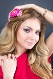 Schönes blondes Mädchen mit hellem Make-up, dem langen Kraushaar und enormem Schmuck auf weißem Hintergrund Art und Weiseschuß Lizenzfreie Stockbilder