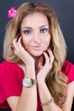 Schönes blondes Mädchen mit hellem Make-up, dem langen Kraushaar und enormem Schmuck auf weißem Hintergrund Art und Weiseschuß Stockfotos