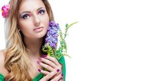 Schönes blondes Mädchen mit hellem Make-up, langes Kraushaar und enorme der Schmuck, die ein Blühen hält, verzweigen sich auf wei Lizenzfreie Stockfotografie