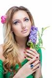 Schönes blondes Mädchen mit hellem Make-up, langes Kraushaar und enorme der Schmuck, die ein Blühen hält, verzweigen sich auf wei Stockfoto