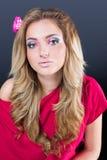 Schönes blondes Mädchen mit hellem Make-up und langes Kraushaar auf grauem Hintergrund Art und Weiseschuß Stockbilder