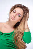 Schönes blondes Mädchen mit hellem Make-up und langes Kraushaar auf weißem Hintergrund Art und Weiseschuß Lizenzfreies Stockfoto