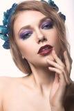 Schönes blondes Mädchen mit hellem Make-up und purpurrote blaue Blumen in ihrem Haar Schönes lächelndes Mädchen Lizenzfreies Stockbild