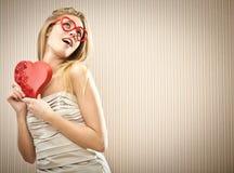 Schönes blondes Mädchen mit Herzgläsern mit Pralinenschachtelliebesgeschenk Stockfoto