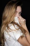 Schönes blondes Mädchen mit ihrem Haar, das ihr Gesicht mit einem Hemdkragen bedeckt und die Kamera betrachtet Lizenzfreies Stockfoto