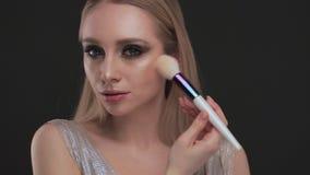 Schönes blondes Mädchen mit Klassiker die Bürste bilden und gegenüberstellen, die im Studio aufwirft Schönes lächelndes Mädchen stock video