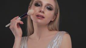 Schönes blondes Mädchen mit Klassiker die Bürste bilden und gegenüberstellen, die im Studio aufwirft Schönes lächelndes Mädchen stock video footage