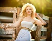 Schönes blondes Mädchen mit Landblick nahe einem alten Bretterzaun am sonnigen Sommertag Lizenzfreies Stockbild