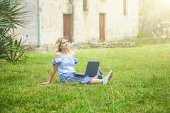 Schönes blondes Mädchen mit Laptop im Park lizenzfreies stockfoto