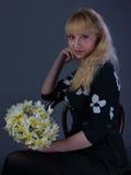 Schönes blondes Mädchen mit Narzissen auf Blau Lizenzfreies Stockbild