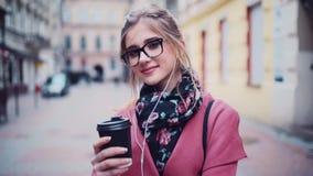 Schönes blondes Mädchen mit natürlichem Make-up und hellem Zubehör, wenn die Kopfhörer den heißen Kaffee zum Mitnehmen halten und stock video footage