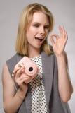 Schönes blondes Mädchen mit rosa Kamera lacht und lächelt Stockfoto