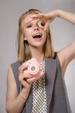 Schönes blondes Mädchen mit rosa Kamera lacht und lächelt Stockbild