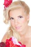 Schönes blondes Mädchen mit roten Blumen Stockfotos