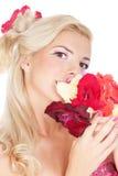 Schönes blondes Mädchen mit roten Blumen Lizenzfreies Stockbild